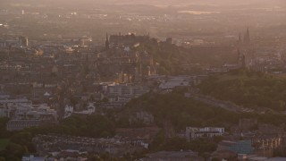 AX112_064 - 6K stock footage aerial video of passing Edinburgh Castle and cityscape, Scotland at sunset