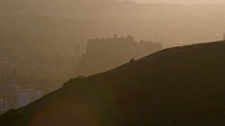 AX112_070 - 6K stock footage aerial video flyby Arthur's Seat, reveal Edinburgh Castle, Scotland at sunset