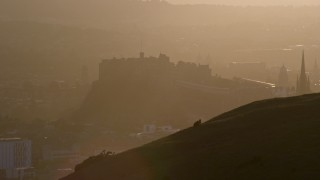 AX112_071 - 6K stock footage aerial video of Edinburgh Castle seen from Arthur's Seat, Scotland at sunset