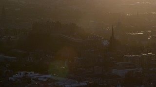 AX112_074 - 6K stock footage aerial video slowly flyby Edinburgh Castle and The Hub cathedral, Scotland at sunset