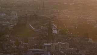 AX112_075 - 6K stock footage aerial video of slowly pass famous Edinburgh Castle and The Hub cathedral, Scotland at sunset
