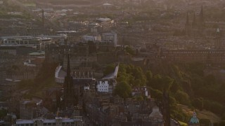 AX112_076 - 6K stock footage aerial video of passing iconic Edinburgh Castle and The Hub cathedral, Scotland at sunset