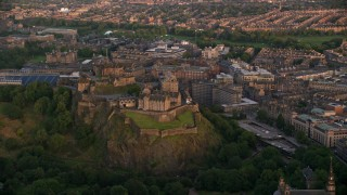 AX112_080 - 6K stock footage aerial video of a view of the famous hilltop Edinburgh Castle, Scotland at sunset