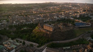 AX112_084 - 6K stock footage aerial video of the cityscape and Edinburgh Castle on a hilltop, Scotland at sunset