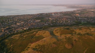 AX112_088 - 6K stock footage aerial video approach residential neighborhoods from Arthur's Seat, Edinburgh, Scotland at sunset
