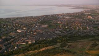 AX112_089 - 6K stock footage aerial video approach residential neighborhoods from Arthur's Seat, Edinburgh Scotland at sunset
