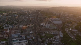 AX112_093 - 6K stock footage aerial video of following Canongate toward Edinburgh Castle, Scotland at sunset