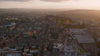 AX112_094 - 6K stock footage aerial video of flying over Canongate toward Edinburgh Castle, Scotland at sunset