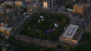 AX112_100 - 6K stock footage aerial video of orbiting George Square Gardens, University of Edinburgh, Scotland at sunset