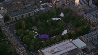 AX112_101 - 6K stock footage aerial video orbit of George Square Gardens with trees, University of Edinburgh, Scotland at sunset