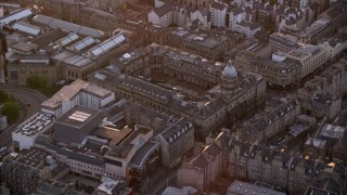AX112_105 - 6K stock footage aerial video of flying by the School of Law at University of Edinburgh, Scotland at sunset