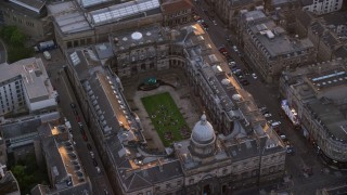 AX112_106 - 6K stock footage aerial video of orbiting University of Edinburgh School of Law, Scotland  at sunset