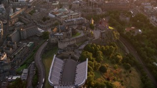 AX112_107 - 6K stock footage aerial video approach and fly over Edinburgh Castle, Scotland at sunset