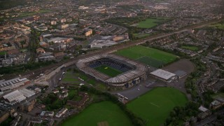 AX112_110 - 6K stock footage aerial video of flying by Murrayfield Stadium, Edinburgh, Scotland at sunset
