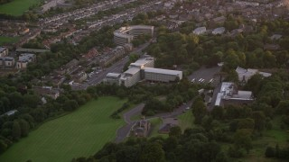 AX112_111 - 6K stock footage aerial video of a t-shaped office building in Edinburgh, Scotland at sunset