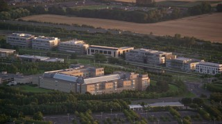 AX112_114 - 6K aerial stock footage video of passing by an office building at sunset in Edinburgh, Scotland