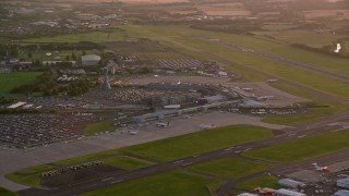 AX112_116 - 6K stock footage aerial video of flying by Edinburgh Airport, Scotland at sunset