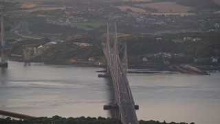 AX112_122 - 6K stock footage aerial video of the Forth Road Bridge, Edinburgh, Scotland at sunset