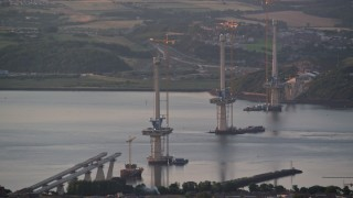 AX112_124 - 6K stock footage aerial video of bridge construction over the Firth of Forth, Edinburgh, Scotland at sunset