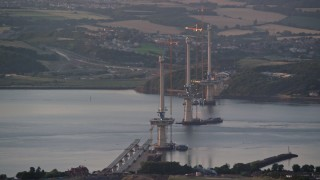 AX112_125 - 6K stock footage aerial video of a bridge under construction over the Firth of Forth, Edinburgh, Scotland at sunset