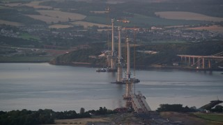 AX112_126 - 6K stock footage aerial video of passing a bridge under construction, Edinburgh, Scotland at sunset