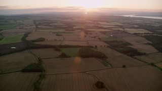 AX112_128 - 6K stock footage aerial video of the setting sun over farmland, Broxburn, Scotland at sunset