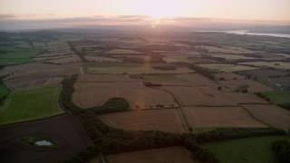 AX112_129 - 6K stock footage aerial video of farm fields with the sun setting, Broxburn, Scotland
