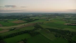 AX112_130 - 6K stock footage aerial video of green farm fields, Broxburn, Scotland at sunset
