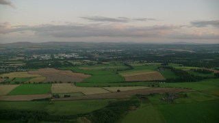 AX112_131 - 6K stock footage aerial video of flying by farming fields at sunset in Broxburn, Scotland