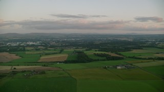 AX112_132 - 6K stock footage aerial video of passing by farm fields at sunset in Broxburn, Scotland