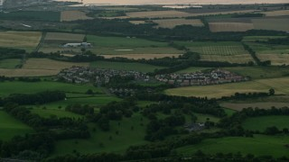 AX112_139 - 6K stock footage aerial video of farmland and rural homes in a village near Falkirk, Scotland at twilight
