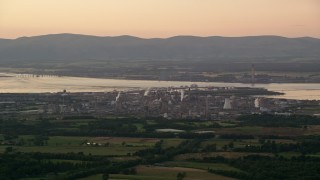 AX112_141 - 6K stock footage aerial video of a natural gas power plant beside the water, Falkirk, Scotland at sunset