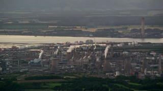 AX112_142 - 6K stock footage aerial video of a natural gas plant by water, Falkirk, Scotland at twilight