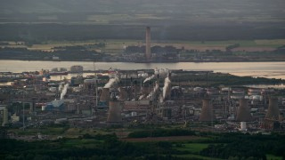 AX112_143 - 6K stock footage aerial video of a natural gas plant overlooking the water, Falkirk, Scotland at twilight