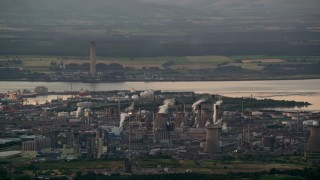 AX112_144 - 6K stock footage aerial video flyby natural gas plant by the water, Falkirk, Scotland at twilight