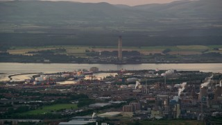 AX112_145 - 6K stock footage aerial video flyby natural gas plant by the water, Falkirk, Scotland at twilight