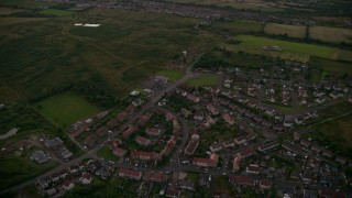 AX112_146 - 6K stock footage aerial video tilt to rural homes by farmland, Falkirk, Scotland at twilight