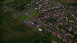 AX112_147 - 6K stock footage aerial video of orbiting rural homes in small village near Falkirk, Scotland at twilight