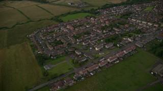 AX112_148 - 6K stock footage aerial video of orbiting rural village homes and farmland, Shieldhill, Scotland at twilight