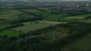 AX112_151 - 6K stock footage aerial video of orbiting radio towers surrounded by farmland, Falkirk, Scotland at twilight