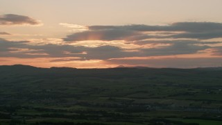 AX112_153 - 6K stock footage aerial video of setting sun behind clouds over Scottish Highlands, Scotland