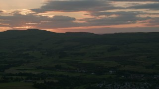 AX112_159 - 6K stock footage aerial video of sun-lit clouds over farms and fields in Bonnybridge, Scotland at twilight