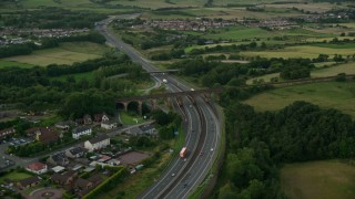AX112_160 - 6K stock footage aerial video of orbiting M80 Highway near rural homes, Cumbernauld, Scotland at twilight
