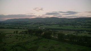 AX112_161 - 6K stock footage aerial video of farmland in a rural landscape at twilight in Cumbernauld, Scotland