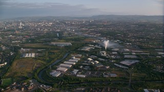AX113_003 - 6K stock footage aerial video of flying away from warehouses and cityscape of Glasgow, Scotland at sunrise