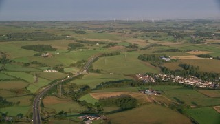 AX113_005 - 6K stock footage aerial video of farms, fields and rural homes near A726 Highway, Glasgow, Scotland at sunrise