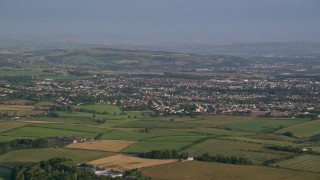 AX113_007 - 6K stock footage aerial video of farms and fields near rural neighborhoods, Glasgow, Scotland at sunrise