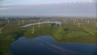 AX113_011 - 6K stock footage aerial video approach windmills and fly over reservoirs, Eaglesham, Scotland at sunrise