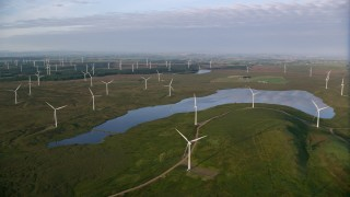 AX113_013 - 6K stock footage aerial video pan across windmills and reservoir, Eaglesham, Scotland at sunrise