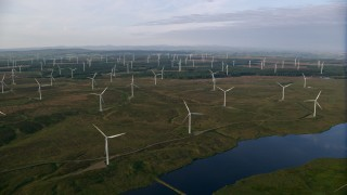 AX113_014 - 6K stock footage aerial video pan across and approach windmills, Eaglesham, Scotland at sunrise